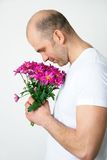 Man with flowers. Romantic man smell at bunch of flowers stock image