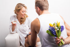 Man with flowers behind his back surprising woman Stock Images
