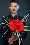 Man with flowers of gerberas Royalty Free Stock Photo
