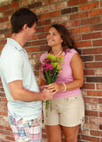Man with flowers for his girlfriend. A young man giving flowers to his girlfriend stock photo