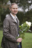 Man with flowers outdoors Stock Photography