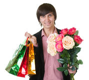 Man with flowers and shopping bags Stock Image
