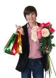 Man with flowers and shopping bags Stock Photography