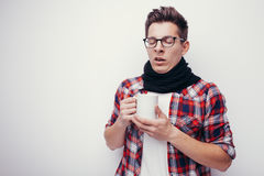 Man with flu and fever wrapped holding cup of healing tea isolated over white. Royalty Free Stock Images