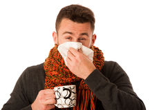 Man with flu and fever wrapped in scarf holding cup of healing t Royalty Free Stock Photography