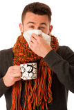 Man with flu and fever wrapped in scarf holding cup of healing t Royalty Free Stock Photos