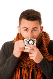Man with flu and fever wrapped in scarf holding cup of healing t Stock Photos