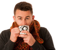 Man with flu and fever wrapped in scarf holding cup of healing t Stock Images
