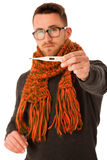 Man with flu and fever wrapped in scarf holding thermometer. Stock Photography