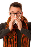 Man with flu and fever wrapped in scarf sneezing into handkerchi Stock Photo