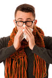 Man with flu and fever wrapped in scarf sneezing into handkerchi Royalty Free Stock Image