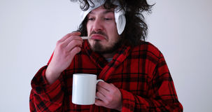 Man with flu and fever. Young Man with flu and fever wrapped holding cup of healing tea isolated over white Royalty Free Stock Image