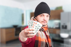 Man with flu holding blisters with pills. As vitamins and flu treatment concept Royalty Free Stock Photography