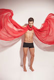 Man fluttering a red textile while looking at the camera Royalty Free Stock Photo