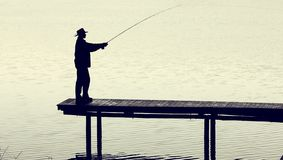 Man with fly-fishing gear catching a trout from jetty on a foggy morning. Man with fly-fishing gear catching a trout from a jetty on a foggy morning stock image