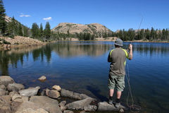 Man fly fishing on lake. Rear view of man fly fishing on lake with Uinta mountains in background, Utah, U.S.A Stock Photo