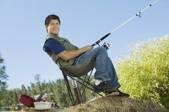 Man fly fishing, sitting on  collapsible chair Royalty Free Stock Image