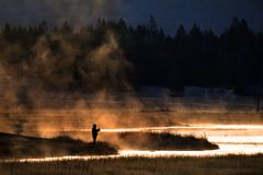 Man Flyfishing in Early Morning Light Mist from River Golden Sun royalty free stock image