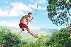 Man flying in the air by rope Stock Images