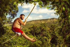 Man flying in the air by rope Royalty Free Stock Images