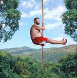 Man flying in the air by rope Royalty Free Stock Photography