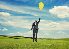 Man flying with balloon at outdoor Royalty Free Stock Photos