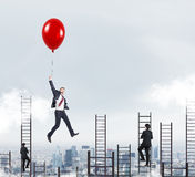 Man flying with balloon over city Royalty Free Stock Photography