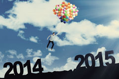 Man flying with balloons above number 2014 to 2015 Stock Photo