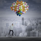 Man flying with balloons Stock Photography