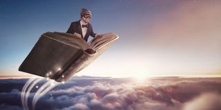 Man flying on a book above the clouds. A man in a suit and googles is flying on book over a picturesque cloud scenery Royalty Free Stock Photo