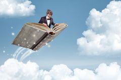 Man flying on a book over the clouds. A man in a suit and bow tie is flying over the clouds whilst sitting on a book Stock Photography
