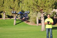 Man Flying A Camera Drone (LARGE FILE). Camera drone flying at a park Royalty Free Stock Images