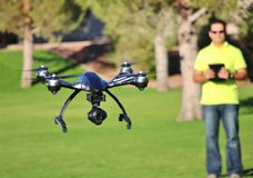 Man Flying A Camera Drone (LARGE FILE). Camera drone flying at a park Stock Photo