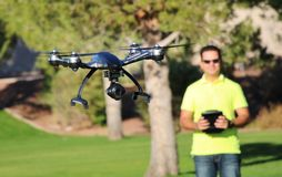 Man Flying A Camera Drone (LARGE FILE). Camera drone flying at a park Stock Images