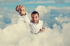 Man flying through the clouds. Super hero businessman with suitcase flying through the clouds Royalty Free Stock Photography