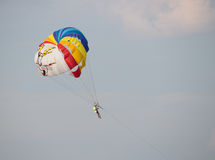 Man flying on a colored parachute at sunset Stock Photography