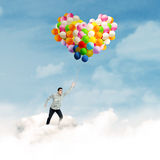 Man flying with colorful balloons Stock Photo