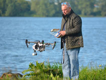 Man flying Drone, Drone in picture, water in background. Royalty Free Stock Images
