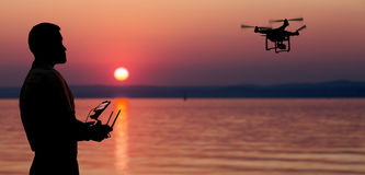 Man flying a drone near at the sunset. Royalty Free Stock Photography