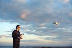 Man flying drone with remote control at the beach. At sunset golden hour royalty free stock photography