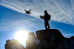 Man flying drone. A silhouette of a man on a rock flying a drone at sunset Stock Images