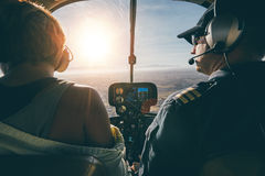 Man flying a helicopter with his copilot Stock Images