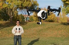 Man Flying A High-Tech Camera Drone (Fall Trees & Leaves in Background) stock photo
