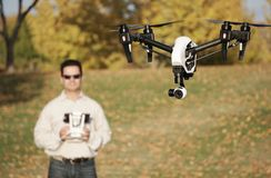 Man Flying A High-Tech Camera Drone (Fall Trees & Leaves in Background). Camera drone flying at a park vector illustration