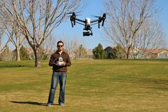 Man Flying a High-Tech Camera Drone. Man flying a drone with a surveillance camera Stock Images