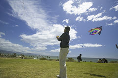 A man flying a kite in a deep blue sky Royalty Free Stock Image