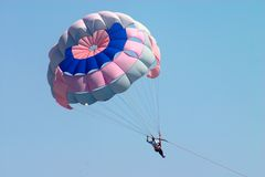 Man flying on parachute Stock Images