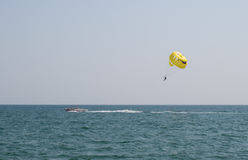 Man flying on a parachute behind above the sea Stock Image