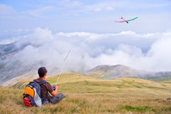 Man flying a plane from a top of the mountain Royalty Free Stock Photo
