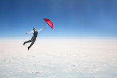 Man flying in the sky with umbrella. Man flying in the sky with red umbrella in his hand Royalty Free Stock Image